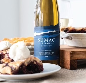 A bottle of Sumac Ridge White next to a piece of pie on a plate.
