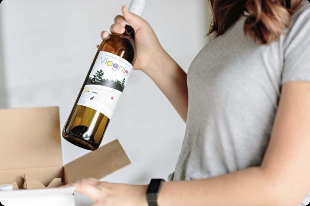 Woman pulling a bottle of Viognier out of a box.